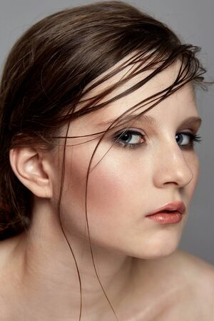 Young fashionable girl with all-day makeup with the effect of wet hair. Grey background. Banque d'images