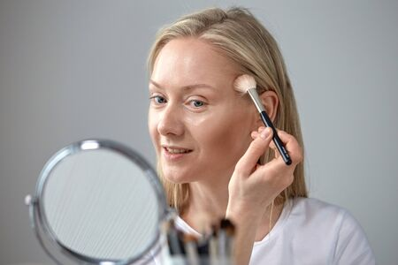 A blonde woman does her own make-up at the mirror. Cosmetic brush in hand. Theres a mirror in the foreground.