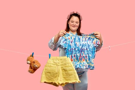 A cheerful housewife holds in her hands a T-shirt next to a rope with washed linen. Bright clothes.