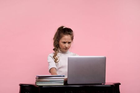 A young girl sitting at a table looks with a sullen face into a computer monitor. Фото со стока