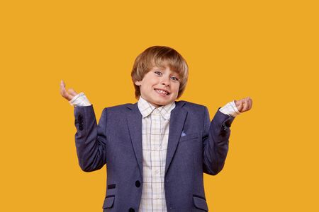 The smiling boy spread his arms to the sides and asks a question. yellow background. Standard-Bild
