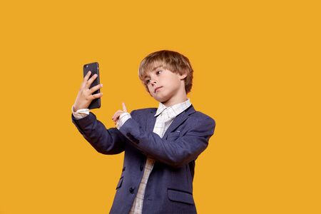 Cute beautiful little boy takes a selfie with a mobile phone in his hands. Yellow background.
