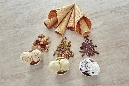 Ice cream is broken down into several ingredients. Balls of ice cream, nuts and wafer horns. Stock Photo