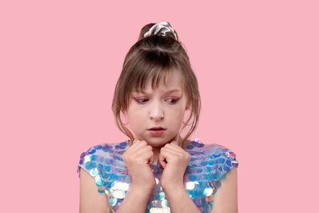 Portrait of a little frightened girl. The girl looks to the bottom and to the side. Pink background. Foto de archivo