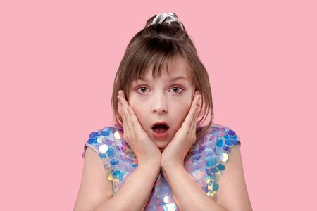 Close up portrait of a scared and anxious young girl looking at camera with eyes wide open, isolated on pink background. Human emotions Stockfoto