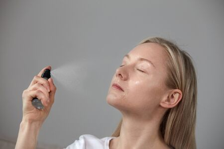 The girl puts the foundation under the makeup of the spray on the face. A clean, beautiful blonde face. Grey background. 写真素材 - 148799859