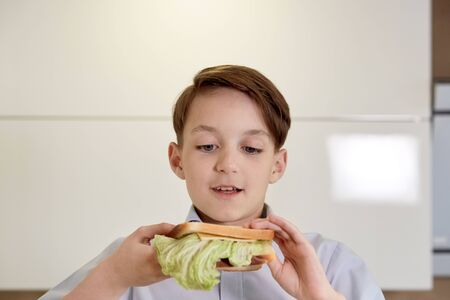 Close-up face of a handsome brunet boy who eats a sandwich. A boy is eating breakfast in front of the school.