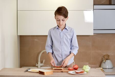 The boy cooks himself breakfast, put the ham on the toast. A child is preparing a sandwich of bread and vegetables. Reklamní fotografie