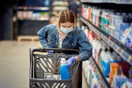Cute girl in a shopping center in a mask lays goods in a basket. Safe shopping during a pandemic.