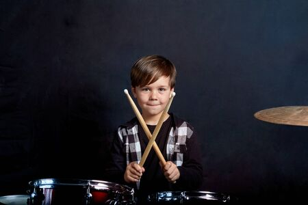 The child sits with drumsticks in his hands. Studying in the studio. Sound recording studio.
