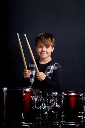 Vertical photo of a child with a musical instrument, drums. the baby is looking at the camera. Dark blue background. Interesting hobby. Standard-Bild