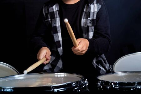 The boy holds drumsticks in his hands. Without a face. Drumming.