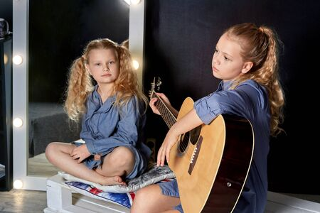 Two beautiful little girls blonde sisters with blue eyes in a cozy setting to learn to play the guitar. Dark background. A fascinating hobby. Stok Fotoğraf