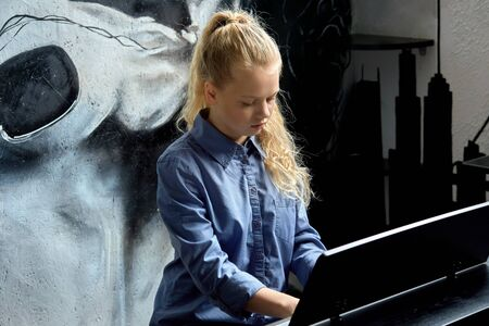Young blonde girl learn to play the piano. Against the background of a wall with a black and white pattern.