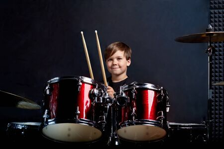 Cheerful smiling child plays the drums. Boys Studios. Dark blue background.