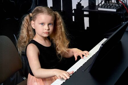 A blonde girl learns to play a musical instrument and looks at the camera. A fascinating hobby. Girl in a beautiful dress.