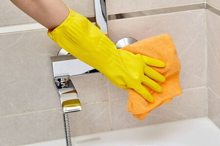 Professional housekeeping. Wipe the faucet in the bathroom with a dry towel. Room cleaning.