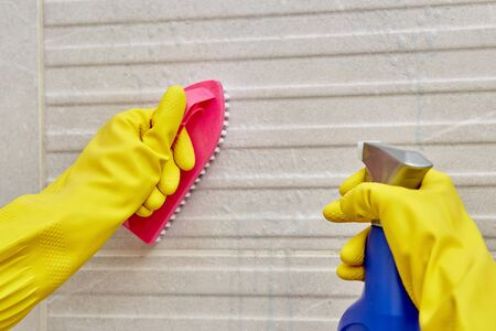 Female hand in a protective yellow glove with a brush and spray with household chemicals. Cleaning the bathroom. Wash and clean the dirt on the tiles in the bathroom.