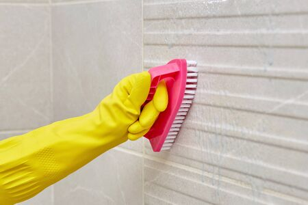 Hand in a yellow rubber protective glove with a brush. Cleaning the bathroom. Wash and clean the dirt on the tiles in the bathroom. Home routine. 写真素材