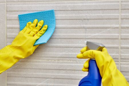 Female hand in a protective yellow glove with a napkin for cleaning and a spray with household chemicals. Cleaning the bathroom. Wash the tiles.