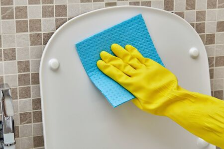 Close-up without a face wash the toilet lid in protective yellow cleaning gloves. Daily routine. Household duties. 写真素材