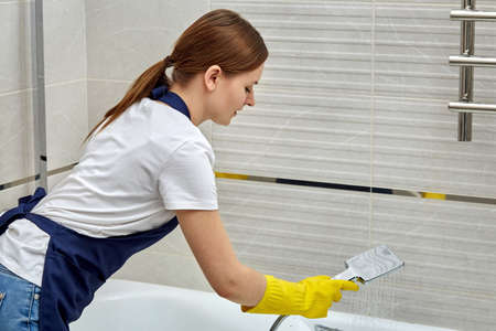 Beautiful young girl provides cleaning service. The girl washes a white bathroom. House cleaning. Daily routine. Фото со стока