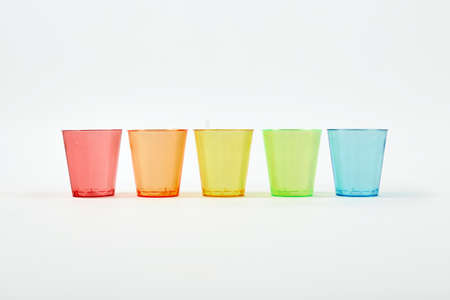 Red, orange, yellow, green, blue. Multi-colored glasses of glass standing in a row on a white background. Recycled material. Caring for the environment.