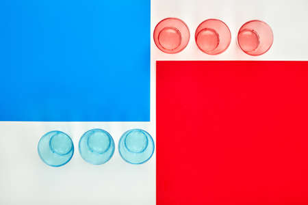 Red and blue glasses near paper of the same color. Place for advertising. Bright photo. Recycled material.