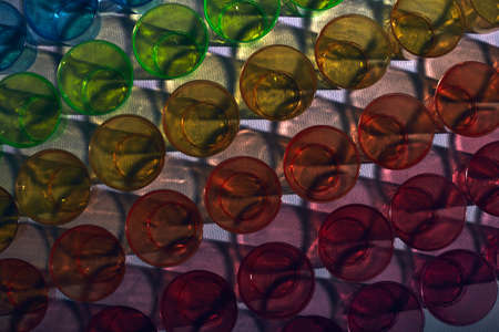 Texture of multi-colored glasses made of plastic with shadows. Nice background. Recycled plastic. Caring for the environment.