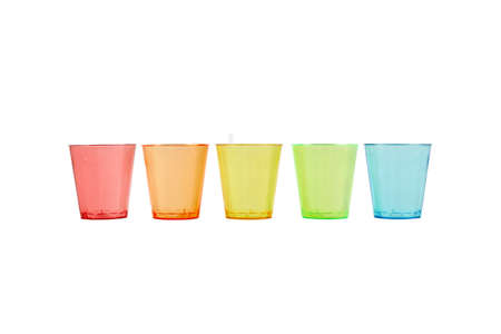 Multi-colored glasses standing in a row on a white background. Recycled material. Caring for the environment.