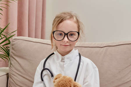 The game of the doctor. A girl in doctor clothes and glasses looks at the camera. The girl is blonde. Archivio Fotografico
