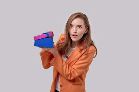 A young beautiful girl with a surprised face looks at the camera with a gift box in her hands. Gifts for the holidays. Gray background. Foto de archivo