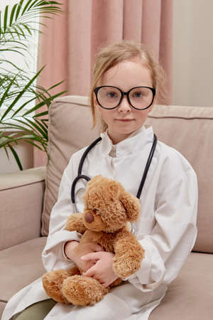 The blonde girl wore a doctor uniform, a stethoscope and glasses. The game of the doctor.