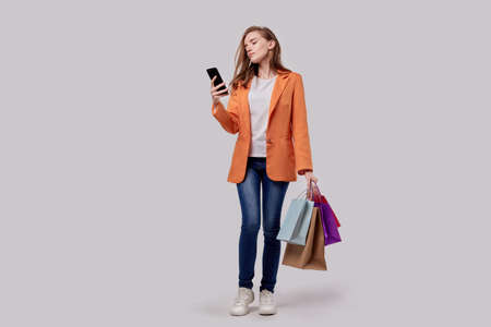 Buy many holiday gifts online. Girl is shopping online. Holds bright shopping bags in his hand. Online shopping. Gray background. Imagens