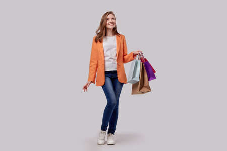 A girl in a bright fashionable jacket and jeans holds in her hand purchases in bags. Joyful face. Gray background. Imagens