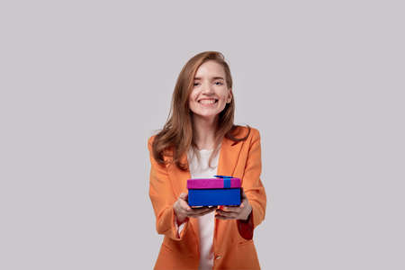 A young girl with a happy face receives a gift in a bright box. Gifts for the holidays. Gray background.