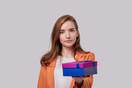 Girl gives a gift in a bright box. Gifts for the holidays. Gray background.