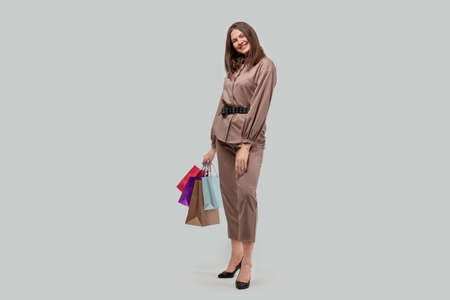A full-length woman holds in her hands purchases with gifts in bags. Buying gifts for the holidays. Gray background.