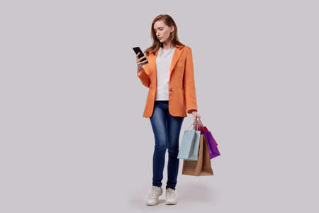 GIRL is shopping online with a cellphone. Holds bright shopping bags in his hand. Online shopping. Gray background. Imagens