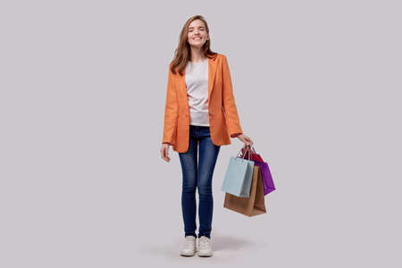 Cute pretty girl is happy with shopping. Good shopping trip. Joyful face. Gray background.
