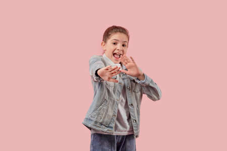 A frightened beautiful girl put her hands forward. The child is protected from violence. Pink background.