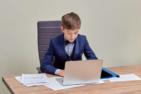Portrait of a serious businessman sitting at the negotiation table. Children are businessmen. Business, formal suit.