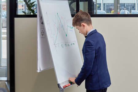 Young handsome businessman drew a graph on the blackboard. The guy has his back.
