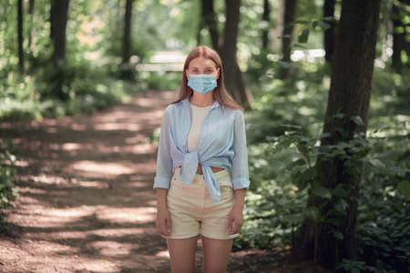 Beautiful young girl in a medical mask in the park. Summer park.