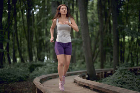 Happy brunette girl in shorts and a tank top runs in a summer park. Outdoor sports. Foto de archivo