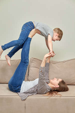 A young mother lifted her child up and plays with him. Happy child. Vertical photo.