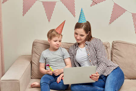 Mom and child communicate via video link with relatives. Celebrating the birthday of the child.