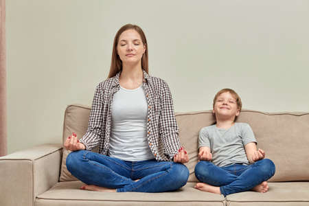 Yoga class at home with a child. A young mother teaches her child how to meditate correctly. Happy healthy family. Standard-Bild