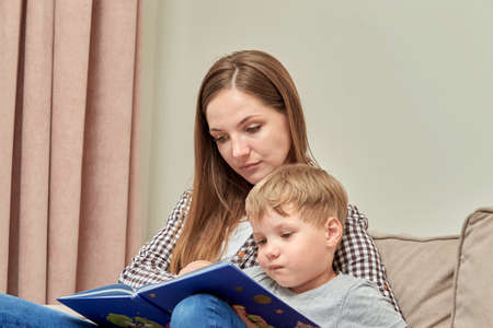 A young mother teaches her preschool son to read. Open book. Home schooling.
