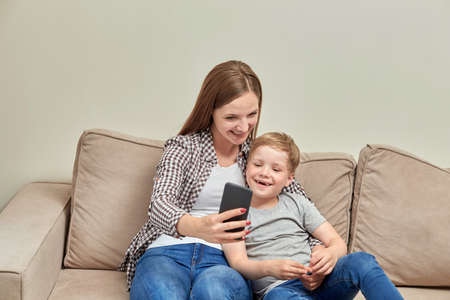 Young beautiful mother communicates online while sitting next to her son. Video call. Online communication.